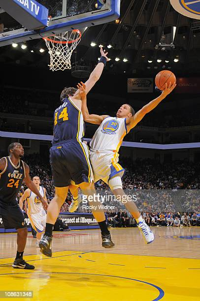 Stephen Curry of the Golden State Warriors throws up a circus shot against Kyrylo Fresenko of the Utah Jazz on January 30 2011 at Oracle Arena in...