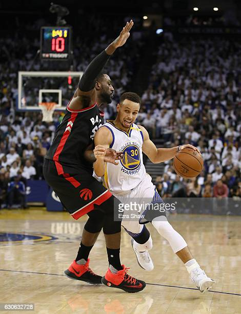 Stephen Curry of the Golden State Warriors tries to dribble past Patrick Patterson of the Toronto Raptors at ORACLE Arena on December 28 2016 in...