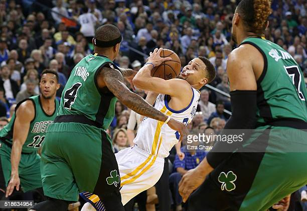 Stephen Curry of the Golden State Warriors tries to get a shot off while guarded by Isaiah Thomas of the Boston Celtics at ORACLE Arena on April 1...