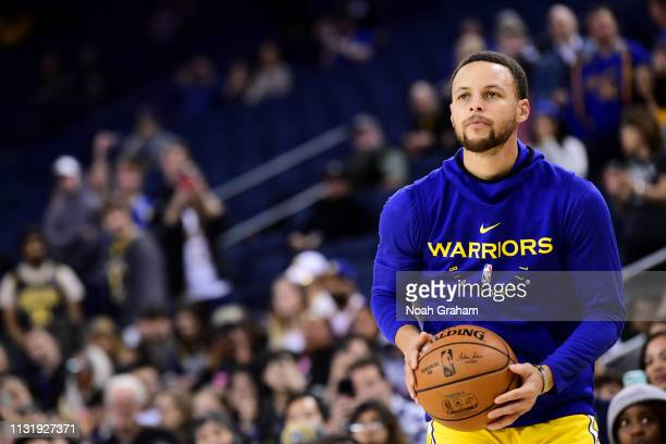 Stephen Curry of the Golden State Warriors warms up before the game against the Indiana Pacers on March 21 2019 at ORACLE Arena in Oakland California...