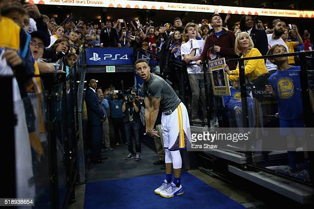 Stephen Curry of the Golden State Warriors watches his ceremonial warmup shot from the hallway go in the basket before their game against the...