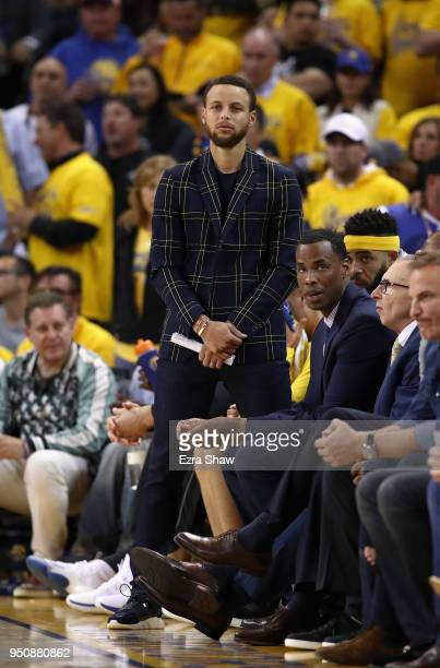Stephen Curry of the Golden State Warriors watches his team from the bench during their game against the San Antonio Spurs in Game 2 of Round 1 of...
