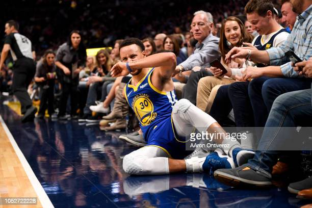 Stephen Curry of the Golden State Warriors winces after falling to the ground upon absorbing contact against the Denver Nuggets during the second...