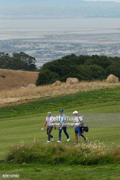 Stephen Curry walks the eighteenth fairway with playing partner Stephan Jaeger of Germany and Curry's caddie Jonnie West during round one of the...