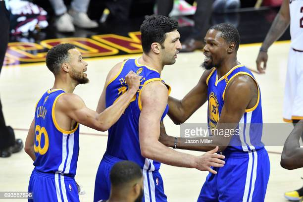 Stephen Curry Zaza Pachulia and Kevin Durant of the Golden State Warriors react after a play in the first half against the Cleveland Cavaliers in...