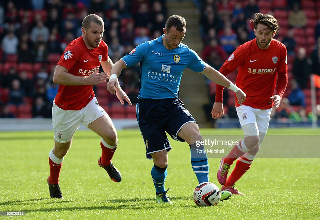 Stephen Dawson and Tom Kennedy of Barnsley chase Noel Hunt of Leeds United during the Sky Bet Championship match between Barnsley and Leeds United at Oakwell on April 19, 2014 in Barnsley, England,