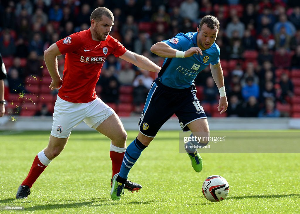 Stephen Dawson of Barnsley tackles Noel Hunt of Leeds United during the Sky Bet Championship match between Barnsley and Leeds United at Oakwell on April 19, 2014 in Barnsley, England,