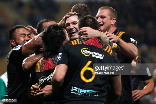 Stephen Donald of the Chiefs celebrates with teammates after scoring a try during the round 11 Super Rugby match between the Chiefs and the Reds at...