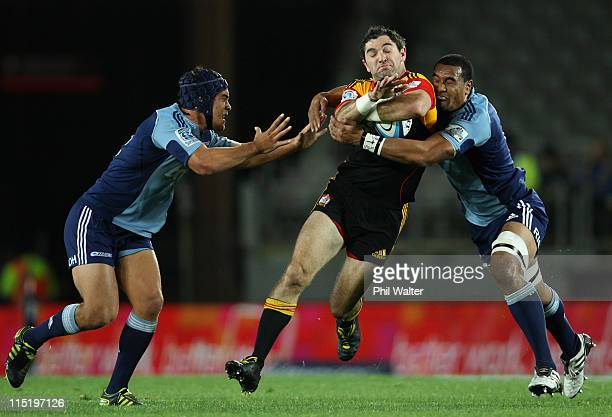 Stephen Donald of the Chiefs is tackled by Jerome Kaino and Benson Stanley of the Blues during the round 16 Super Rugby match between the Blues and...