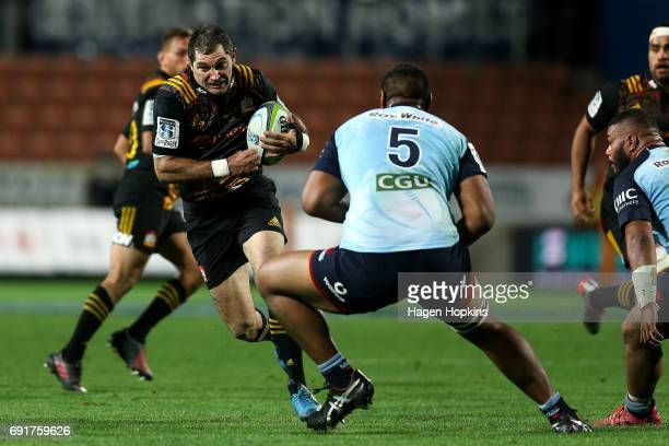 Stephen Donald of the Chiefs runs into the defence of Will Skelton of the Waratahs in his 100th game for the Chiefs during the round 15 Super Rugby...