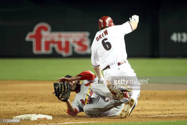 Stephen Drew of the Arizona Diamondbacks collides with relief pitcher Brian Tallet of the St Louis Cardinals as he is tagged out at first base during...