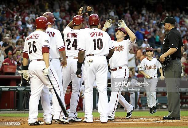 Stephen Drew of the Arizona Diamondbacks highfives teammates Chris Young Justin Upton Kelly Johnson and Miguel Montero after Drew hit a grand slam...