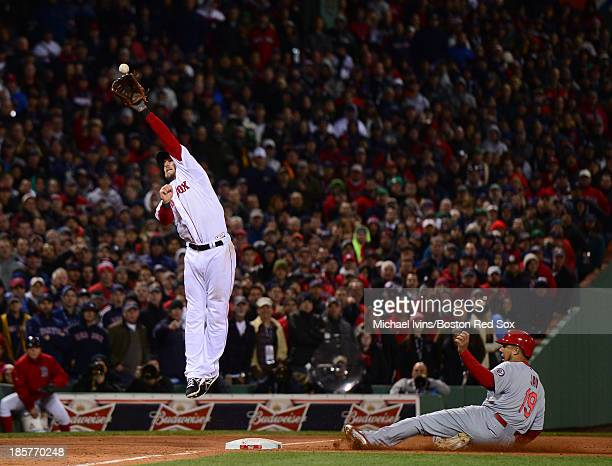 Stephen Drew of the Boston Red Sox attempts to catch an errant throw as Jon Jay of the St Louis Cardinals slides into third base in the seventh...