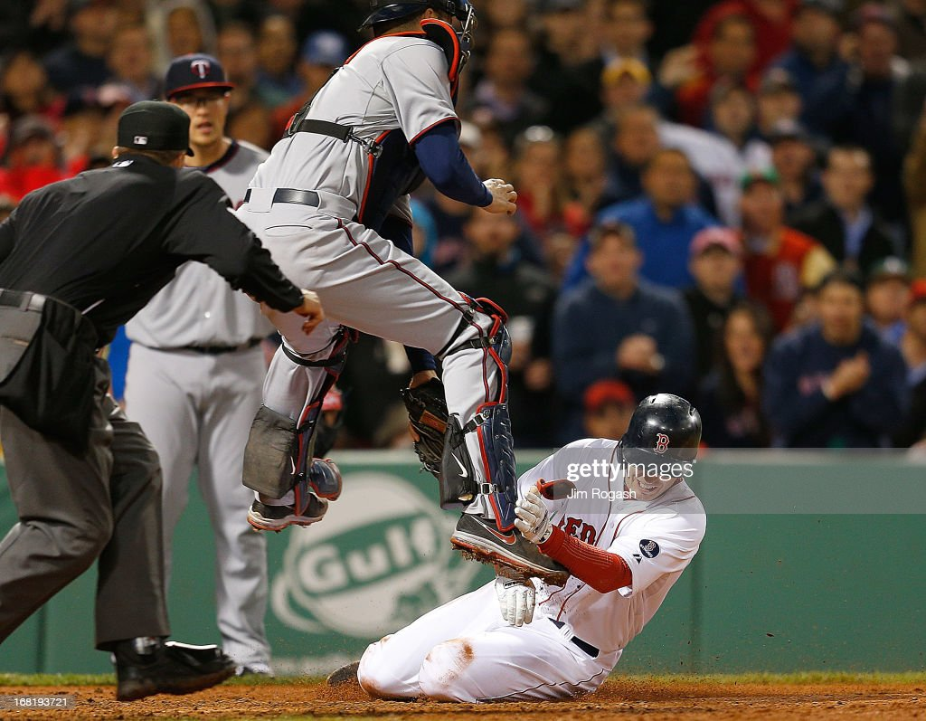 Stephen Drew #7 of the Boston Red Sox is out at the plate as Joe Mauer #7 of the Minnesota Twins leaps for a throw and tags out Drew in the 5th inning at Fenway Park on May 6, 2013 in Boston, Massachusetts.