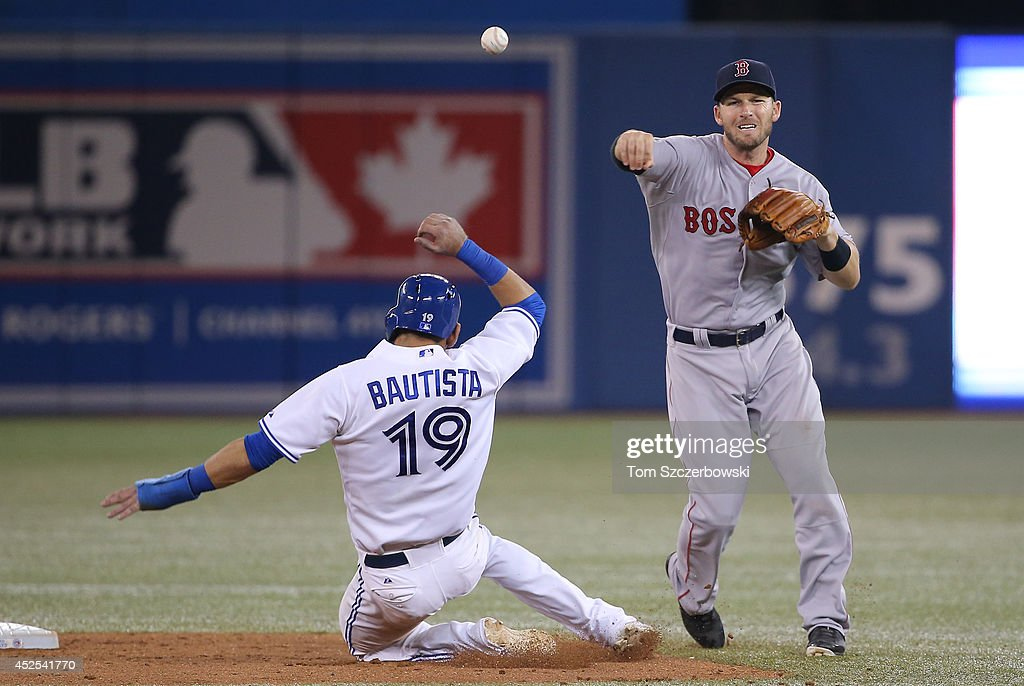 Stephen Drew #7 of the Boston Red Sox turns a double play in the seventh inning during MLB game action as Jose Bautista #19 of the Toronto Blue Jays slides into second base on July 22, 2014 at Rogers Centre in Toronto, Ontario, Canada.