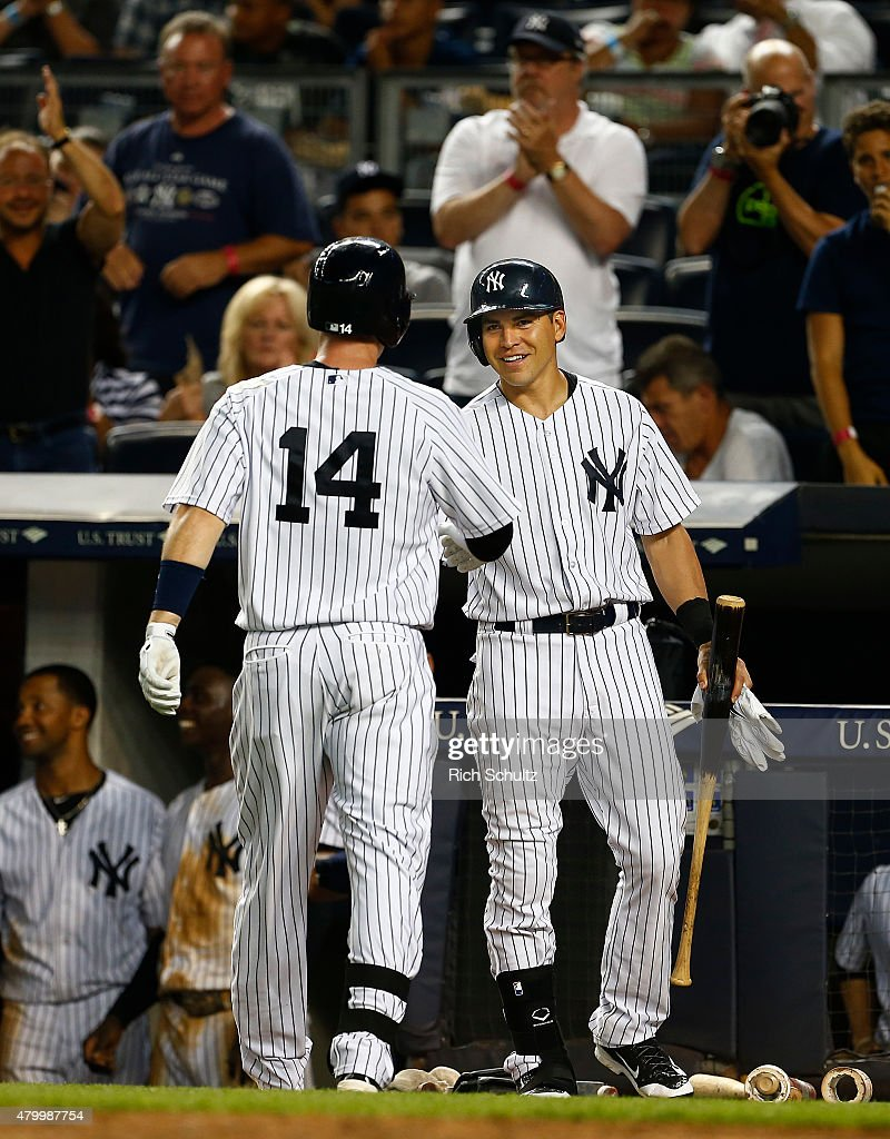 Stephen Drew #14 of the New York Yankees is congratulated Jacoby Ellsbury after he hit a home run in the eighth inning against the Oakland Athletics during a MLB baseball game at Yankee Stadium on July 8, 2015 in the Bronx borough of New York City. The Yankees defeated the A's 5-4.