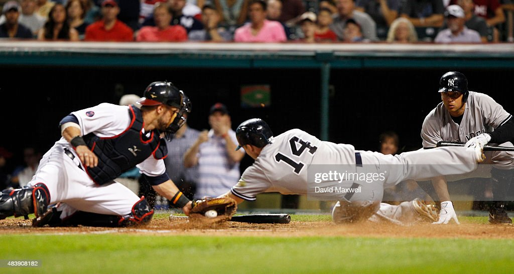 Stephen Drew #14 of the New York Yankees scores ahead of the tag attempt by Yan Gomes #4 of the Cleveland Indians as Alex Rodriguez #13 looks on during the sixth inning of their game on August 13, 2015 at Progressive Field in Cleveland, Ohio. The Yankees defeated the Indians 8-6.
