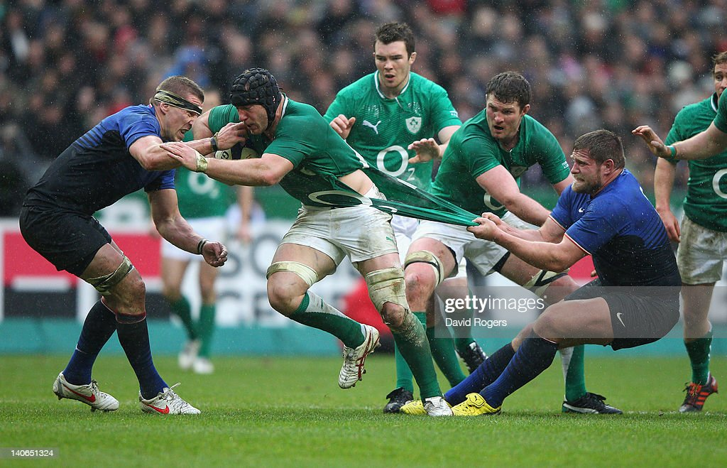Stephen Ferris of Ireland is held by Vincent Debarty during the RBS Six Nations match between France and Ireland at Stade de France on March 4, 2012 in Paris, France.