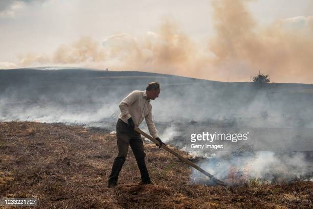 Stephen Frost, a farmer, attempts to beat back a wildfire spreading across the moorland towards his farm, pictured in the Clwydian Range, above the...