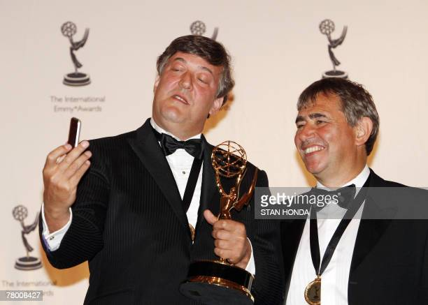 Stephen Fry takes a cell phone photograph of himself and Ross Wilson of Britain after they won for 'The Secret Life of the Manic Depresive' in the...
