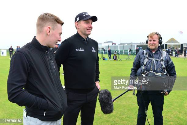 Stephen Gallacher of Scotland and his son and caddie Jack Gallacher are interviewed during previews for the Alfred Dunhill Links Championship at The...