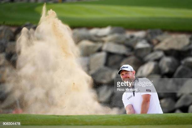 Stephen Gallacher of Scotland plays his second shot from a bunker on the seventh hole during round one of the Abu Dhabi HSBC Golf Championship at Abu...