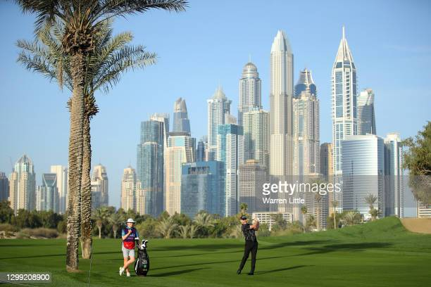 Stephen Gallacher of Scotland plays his second shot on the 13th hole as his caddie Jack Gallagher looks onduring Day Two of the Omega Dubai Desert...