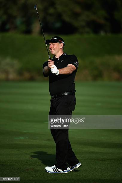 Stephen Gallacher of Scotland plays his third shot ointo the 18th green during the final round of the Omega Dubai Desert Classic on the Majlis Course...