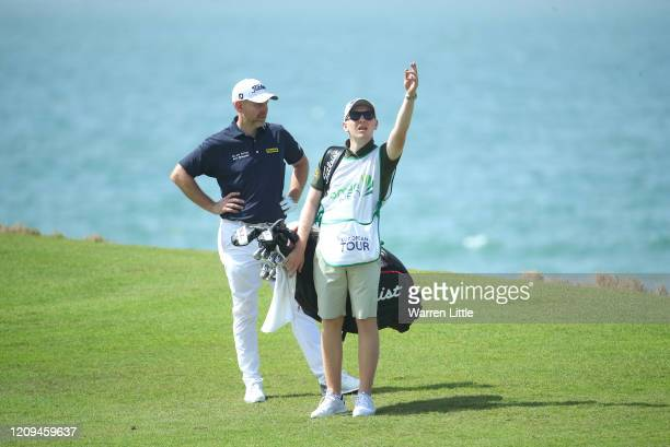 Stephen Gallacher of Scotland plays into the ninth green watched by son and caddie Jack during the third round of the Oman Open at Al Mouj Golf on...