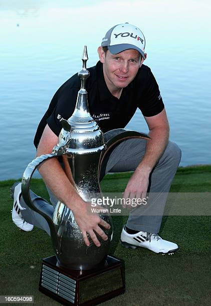 Stephen Gallacher of Scotland poses with the trophy after winning the Omega Dubai Desert Classic at Emirates Golf Club on a score of -22 under par on...