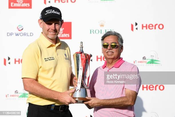 Stephen Gallacher of Scotland poses with the trophy and Pawan Munjal of HERO during the final round on day four of the Hero Indian Open at the DLF...