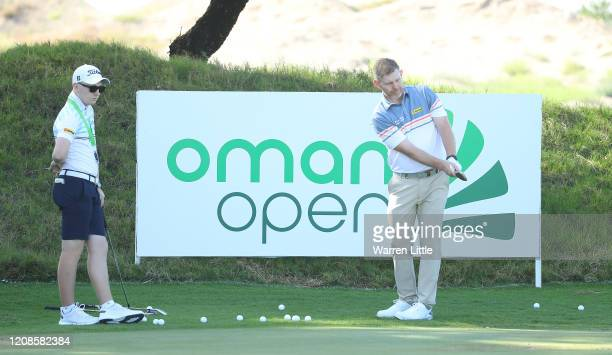 Stephen Gallacher of Scotland practrices watched by his son and caddie Jack Gallacher ahead of the Oman Open at Al Mouj Golf Complex on February 25...