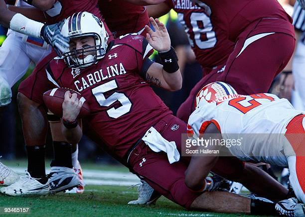 Stephen Garcia of the South Carolina Gamecocks is tackled by Kevin Alexander of the Clemson Tigers at WilliamsBrice Stadium on November 28 2009 in...