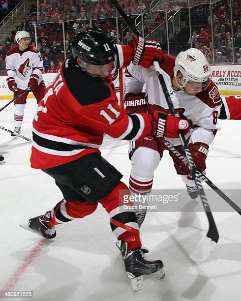 Stephen Gionta of the New Jersey Devils gets the stick up on Mikkel Boedker of the Phoenix Coyotes during the second period at the Prudential Center...