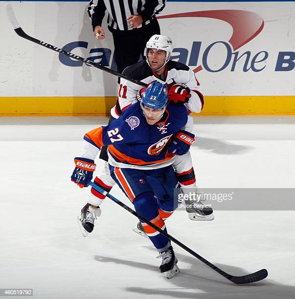 Stephen Gionta of the New Jersey Devils hits Anders Lee of the New York Islanders at the Nassau Veterans Memorial Coliseum on December 15, 2014 in...