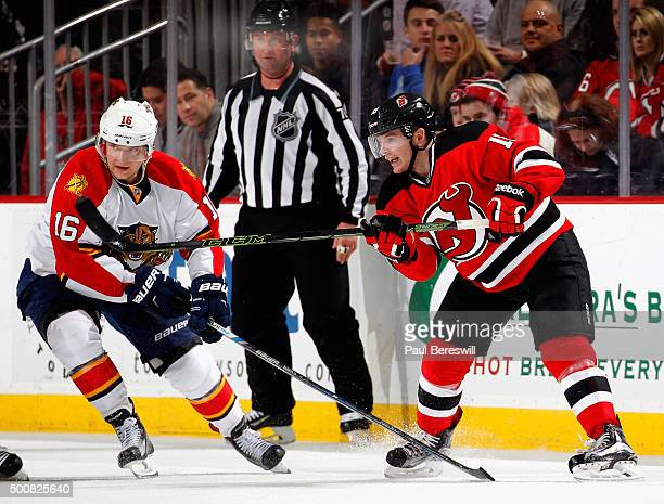 Stephen Gionta of the New Jersey Devils passes the puck in front of Aleksander Barkov of the Florida Panthers during an NHL hockey game at Prudential...