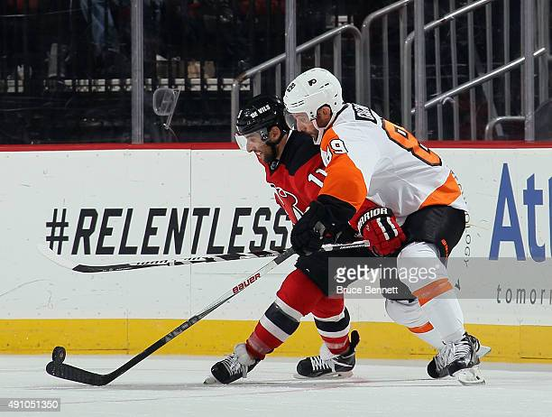 Stephen Gionta of the New Jersey Devils wards off Sam Gagner of the Philadelphia Flyers during the second period at the Prudential Center on October...