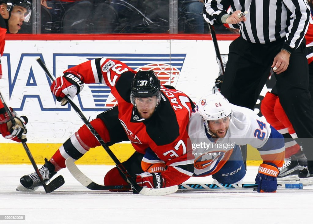 Stephen Gionta #24 of the New York Islanders and Pavel Zacha #37 of the New Jersey Devils get tangled up during the first period faceoff at the Prudential Center on April 8, 2017 in Newark, New Jersey.
