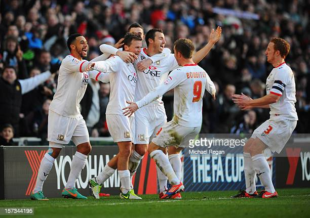 Stephen Gleeson of MK Dons celebrates with team mates as he scores their first goal during the FA Cup with Budweiser Second Round match between MK...