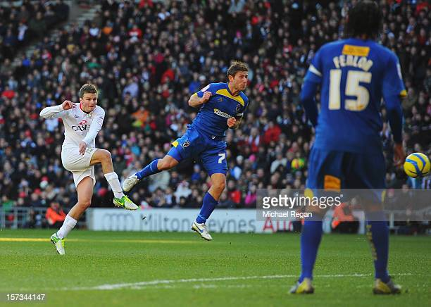 Stephen Gleeson of MK Dons shoots past Stacy Long of AFC Wimbledon to score their first goal during the FA Cup with Budweiser Second Round match...