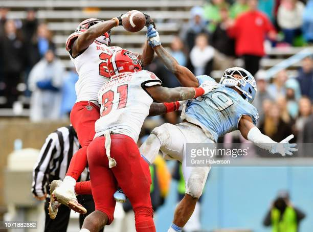 Stephen Griffin and Jarius Morehead of the North Carolina State Wolfpack break up a pass intended for Dazz Newsome of the North Carolina Tar Heels...