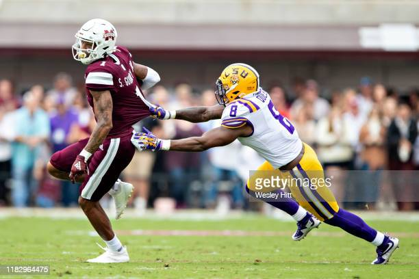 Stephen Guidry of the Mississippi State Bulldogs is grabbed from behind by Patrick Queen of the LSU Tigers at Davis Wade Stadium on October 19 2019...