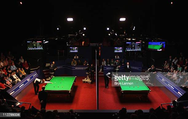 Stephen Hendry of Scotland plays a shot against Joe Perry of England as Ronnie O'Sullivan of England plays a shot against Dominic Dale of Wales in...