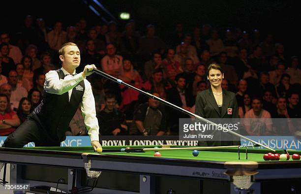Stephen Hendry of Scotland uses the rest and extension to play a shot as referee Michaela Tabb watches in his match against Shaun Murphy of England...