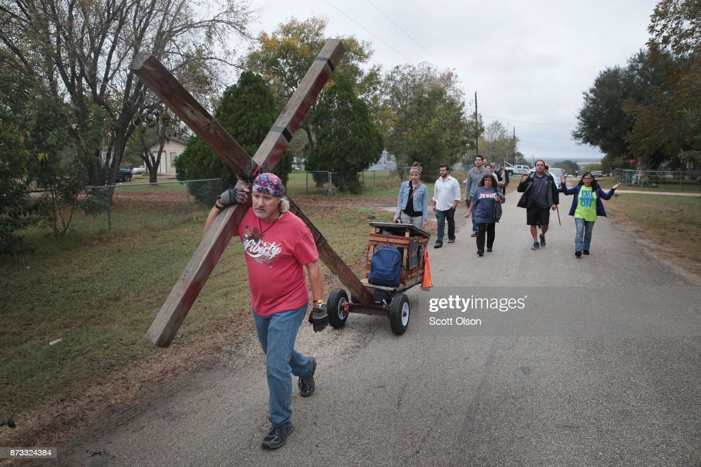 Stephen Hope pulls a cross through town followed by other worshipers after leaving Sunday service at the temporary First Baptist Church of Sutherland Springs on November 12, 2017 in Sutherland Springs, Texas. The service was held in a tent on the site of the town's baseball field. Residents of the community are still trying to heal following the shooting at the original church building on November 5. Devin Patrick Kelley shot and killed the 26 people and wounded 20 others when he opened fire during Sunday service at the church.