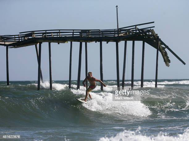 Stephen Hunter Hicks surfs near the Hatteras Pier damaged in previous hurricanes July 2 2014 in Cape Hatteras North Carolina A hurricane warning has...