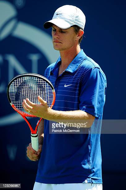 Stephen Huss of Australia examines his racquet during a break in play during his doubles match with Ashley Fisher of Australia against Martin Emmrich...