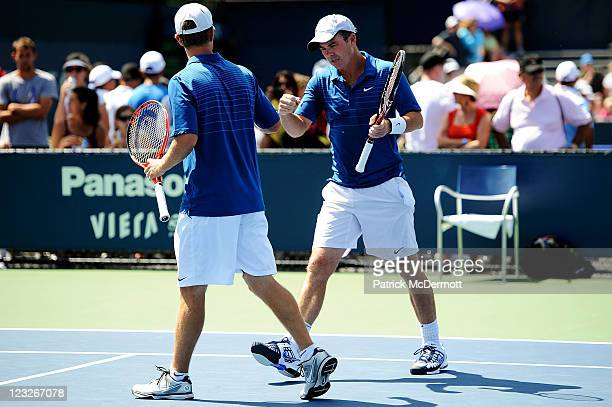 Stephen Huss of Australia of Australia and Ashley Fisher of Australia bump fists during their doubles match against Martin Emmrich of Germany and...