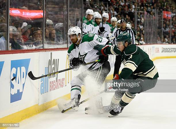 Stephen Johns of the Dallas Stars passes the puck along the boards and away from Charlie Coyle of the Minnesota Wild during the second period of Game...
