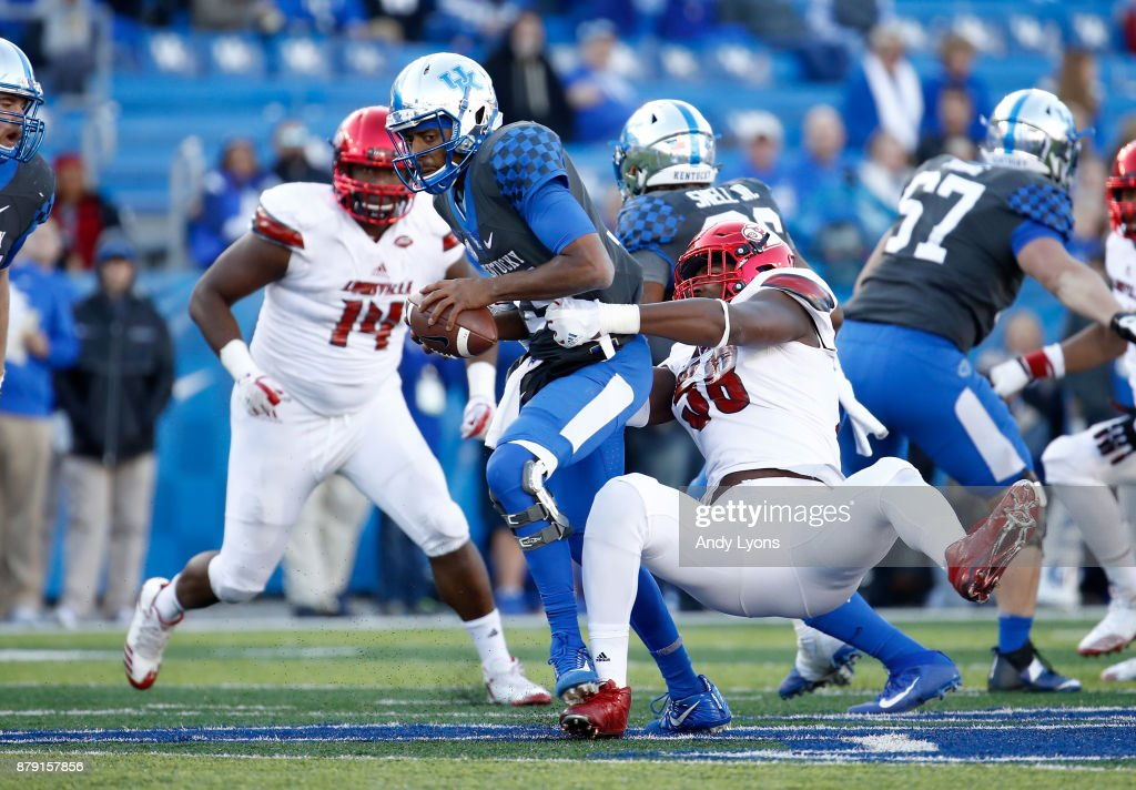 Stephen Johnson #15 of the Kentucky Wildcats is sacked by Jonathan Greenard #58 of the Louisville Cardinals during the game at Commonwealth Stadium on November 25, 2017 in Lexington, Kentucky.